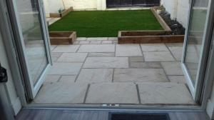 Sandstone patio and flower beds